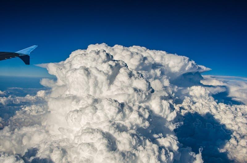 Aeroplano que pasa por la nube de cumulonimbus enorme fotografía de archivo
