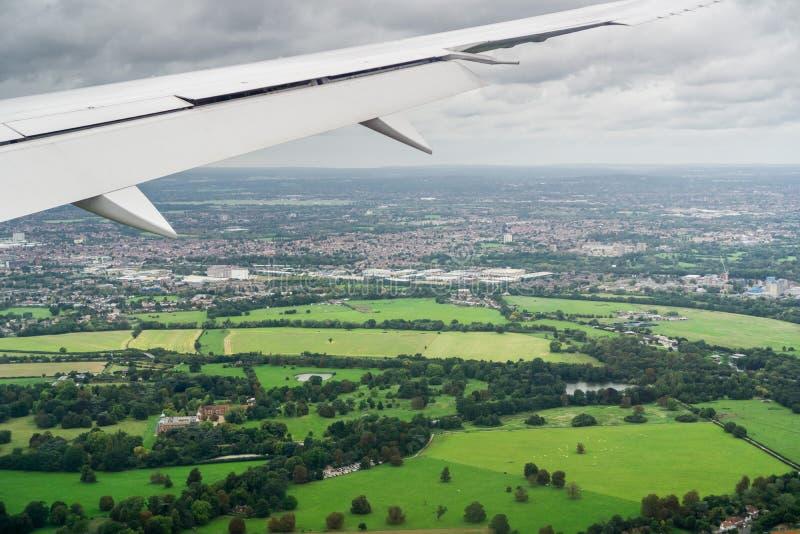 Aeroplano que vuela sobre los campos verdes cerca Londres foto de archivo