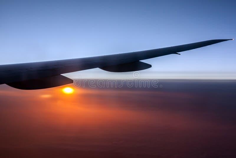 Aeroplano sobre el sol y las nubes imagenes de archivo