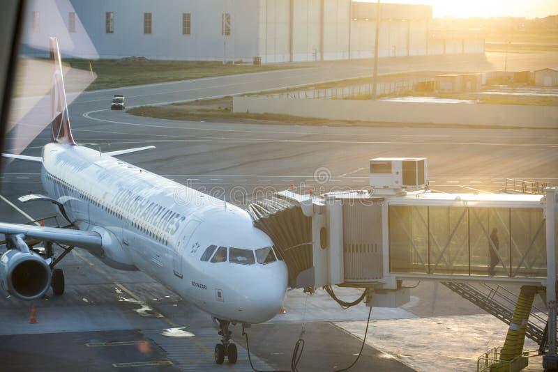Aeroplano vicino al terminale in un aeroporto immagini stock libere da diritti