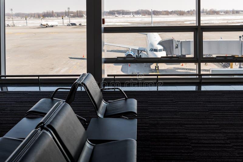 Aeroplano, visión desde el terminal de aeropuerto con los sitios vacíos en la sala de espera del aeropuerto cerca de la puerta co foto de archivo libre de regalías