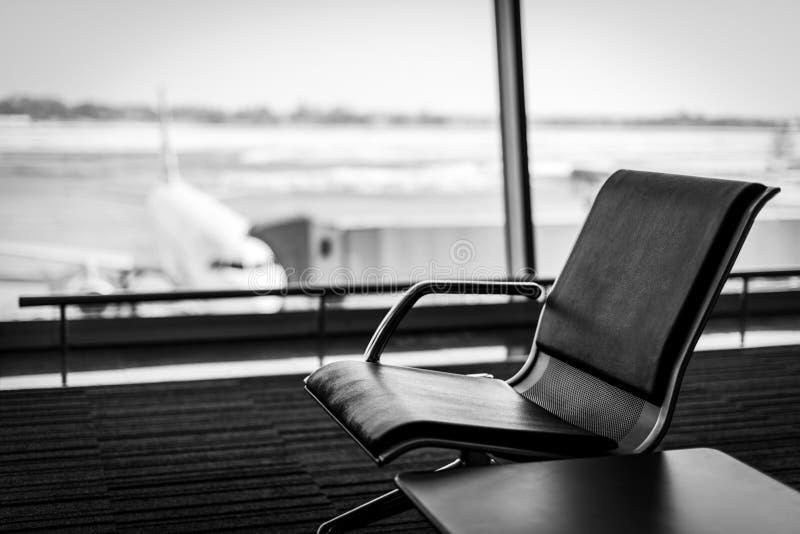 Aeroplano, visión desde el terminal de aeropuerto con los sitios vacíos en la sala de espera del aeropuerto cerca de la puerta Co fotos de archivo