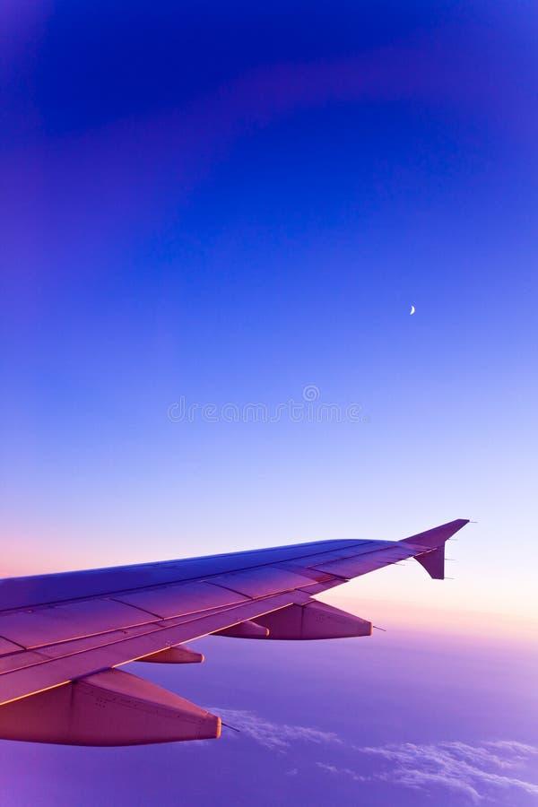 Aeroplano y luna en el cielo de los colores del gradiente imagen de archivo libre de regalías