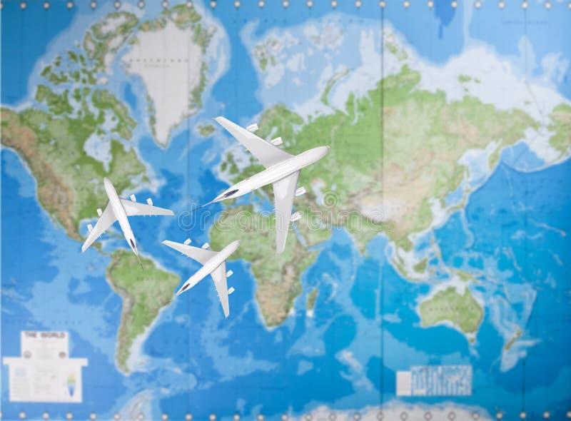Aeroplanos modelo que vuelan en diversa dirección sobre mapa del mundo foto de archivo
