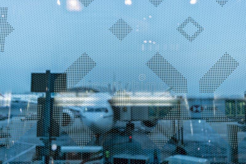 Aeroporto atrás do vidro com o avião e o material de aviação borrados imagem de stock royalty free