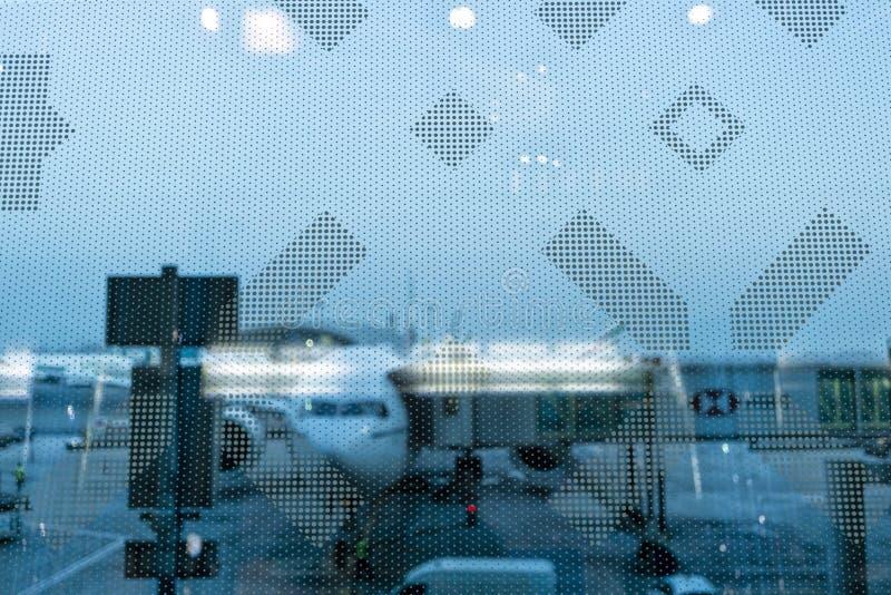 Aeroporto atrás do vidro com o avião e o material de aviação borrados fotos de stock royalty free