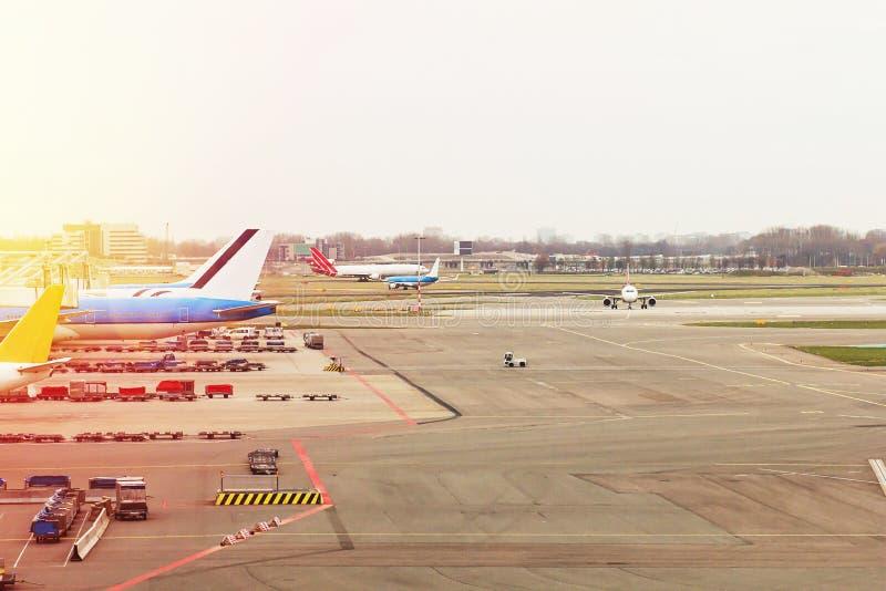 Aeroporto com os aviões na porta terminal pronta para a decolagem, aeroporto internacional durante o por do sol fotografia de stock