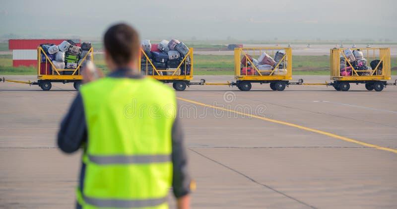 Aeroporto dei bagagli fuori del bagaglio della borsa del carrello del lavoratore immagine stock libera da diritti