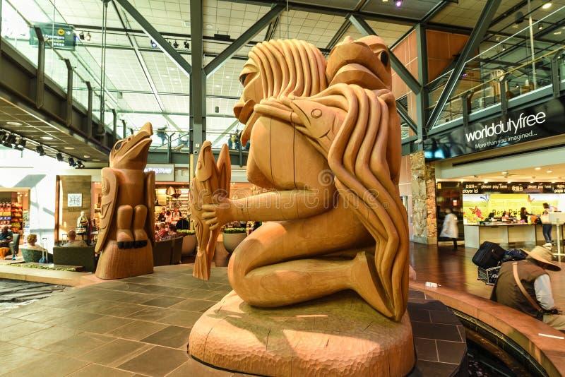 Aeroporto di Vancouver, donna della nebbia della scultura e Raven fotografie stock libere da diritti