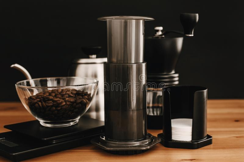 Aeropress, bouilloire en acier, échelles, broyeur manuelle, grains de café sur la table en bois et fond noir Brassage alternatif  images stock