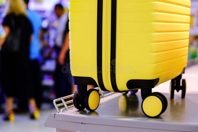 Aeropuerto, maleta amarilla con ruedas en el mostrador En el fondo de la recepción Enfoque suave foto de archivo