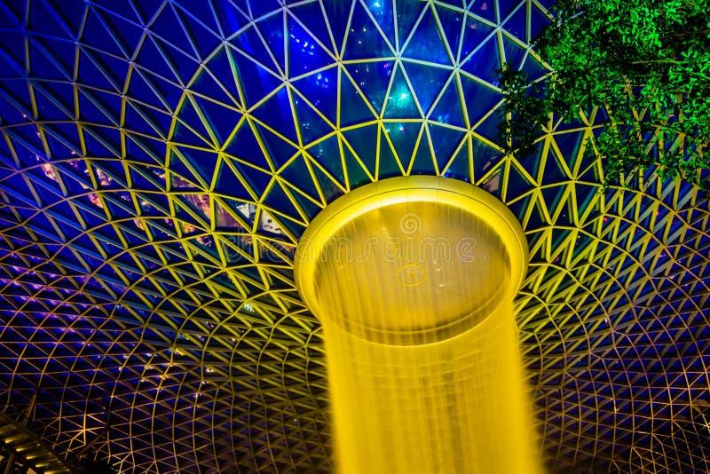 Aeropuerto Singapur - vórtice de Changi de la joya de la lluvia en el cerco de la noche d foto de archivo libre de regalías