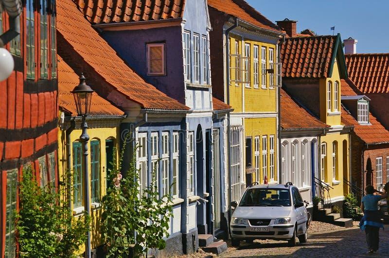 Aeroskobing Danmark - Juli 4th, 2012 - smal kullerstengata på ön av Aero med färgrik historisk bostads- buildin royaltyfri foto
