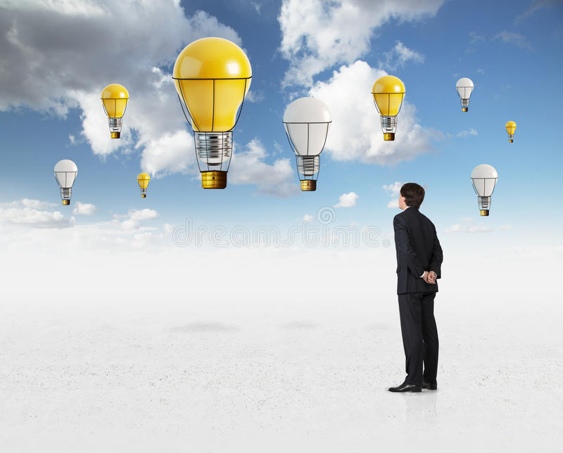 Aerostat in sky. Young businessman looking on aerostat in sky royalty free stock photo