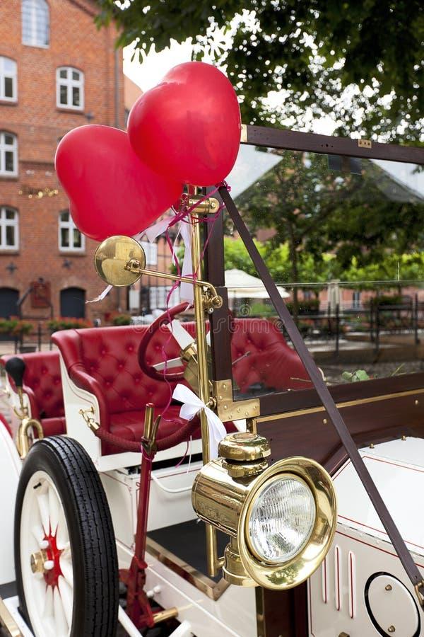 Aerostati del cuore sull'automobile di cerimonia nuziale dell'annata immagine stock libera da diritti