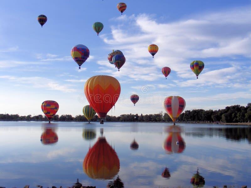 Aerostati di aria calda sopra il lago fotografia stock