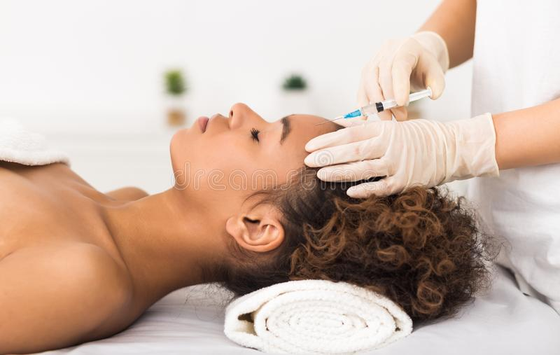Aesthetic surgery. Woman having injection on forehead. In salon, side view stock photo