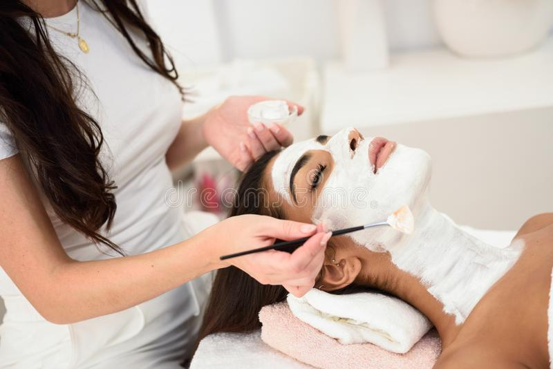 Aesthetics applying a mask to the face of a beautiful woman stock image