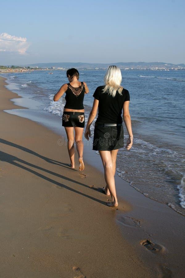 afar девушки пляжа идут 2 стоковые фото