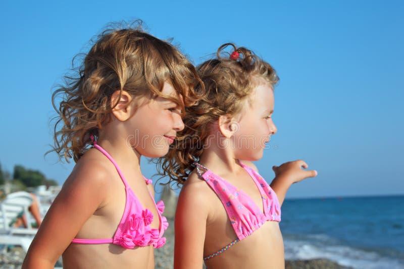 afar девушки пляжа немногая смотря 2 стоковые изображения