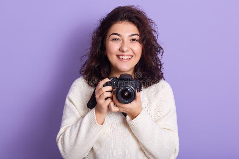 Afbeelding van een emotioneel, gelukkig, krullend vrouwtje dat rechtstreeks naar de camera kijkt, fotocamera vasthoudt, plezier h stock foto