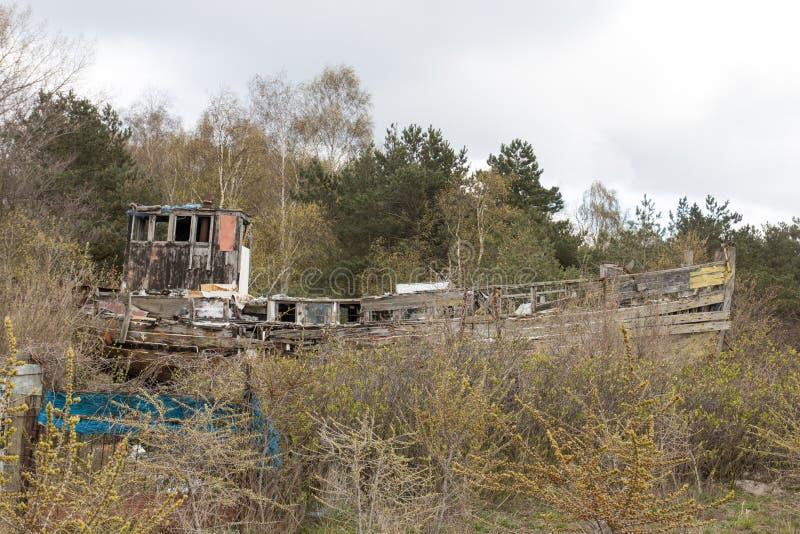 Afbrokkelende houten boot op de kust stock foto's