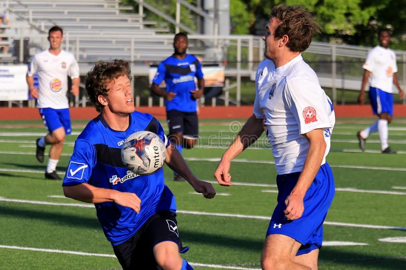 AFC Cleveland Royals game action. Defender gets hit by the ball kicked from the goalie at the professional Soccer event, pro football game, NPSL, National royalty free stock images