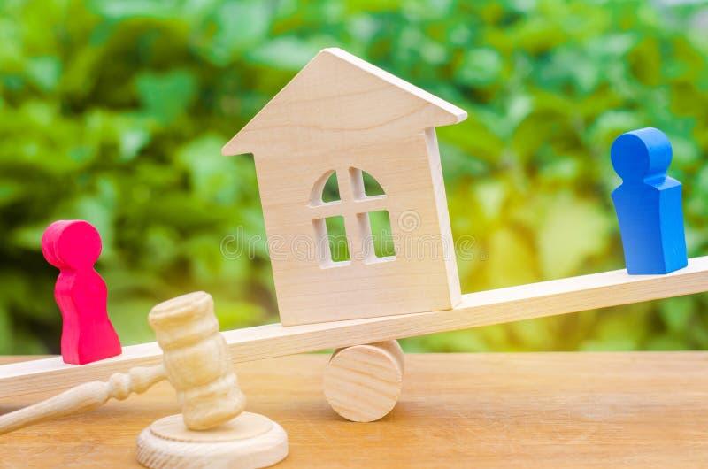 Afdeling van bezit met wettelijke middelen Verduidelijking van eigendom van het huis Houten cijfers van mensen De man en de vrouw stock foto's