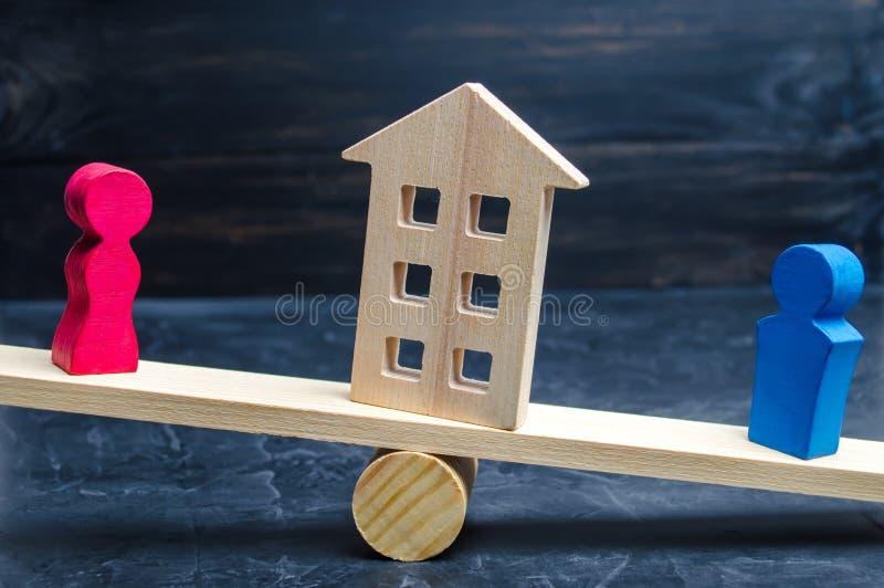 Afdeling van bezit met wettelijke middelen Verduidelijking van eigendom van het huis Houten cijfers van mensen De man en de vrouw royalty-vrije stock foto's