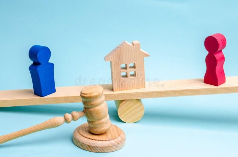 Afdeling van bezit met wettelijke middelen Verduidelijking van eigendom van het huis Houten cijfers van mensen De man en de vrouw stock afbeeldingen