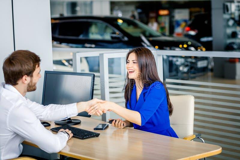 Afdelingschef en vrouwelijke klant het schudden handen die elkaar gelukwensen bij de het handel drijventoonzaal royalty-vrije stock afbeelding