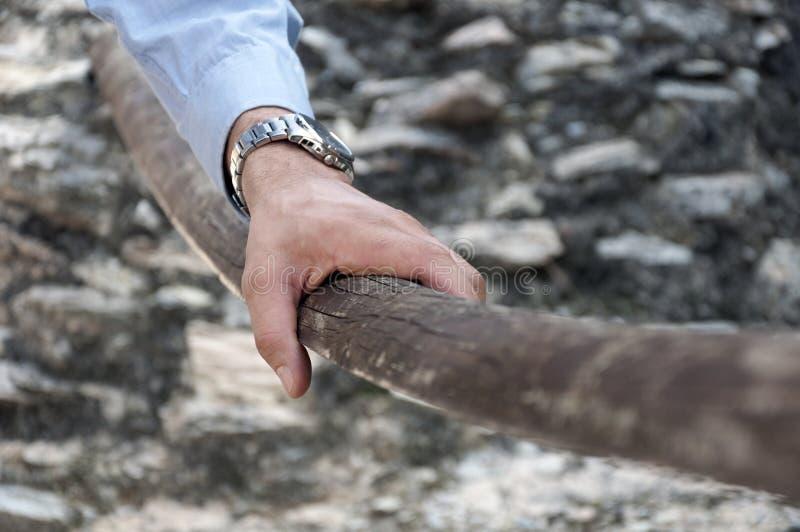 Aferrar masculino de la mano a la barandilla de madera imagen de archivo
