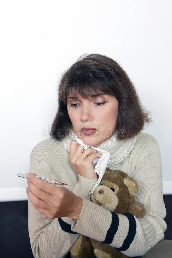 Afetado pela mulher fria olha um termômetro imagens de stock