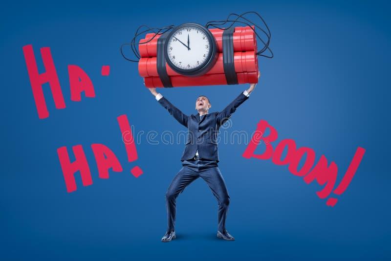 Affärsmannen som rymmer stor röd dynamittid, bombarderar med 'MUMMEL-, MUMMEL- 'och 'BANG'tecken på blå bakgrund fotografering för bildbyråer