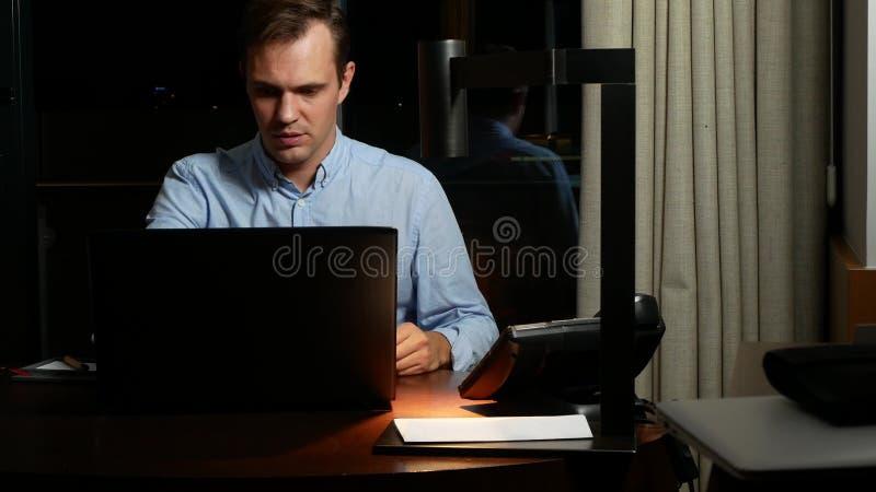 Affär, överansträngningar, stopptid och begrepp av folk - en man som arbetar på en bärbar dator på natten royaltyfri bild