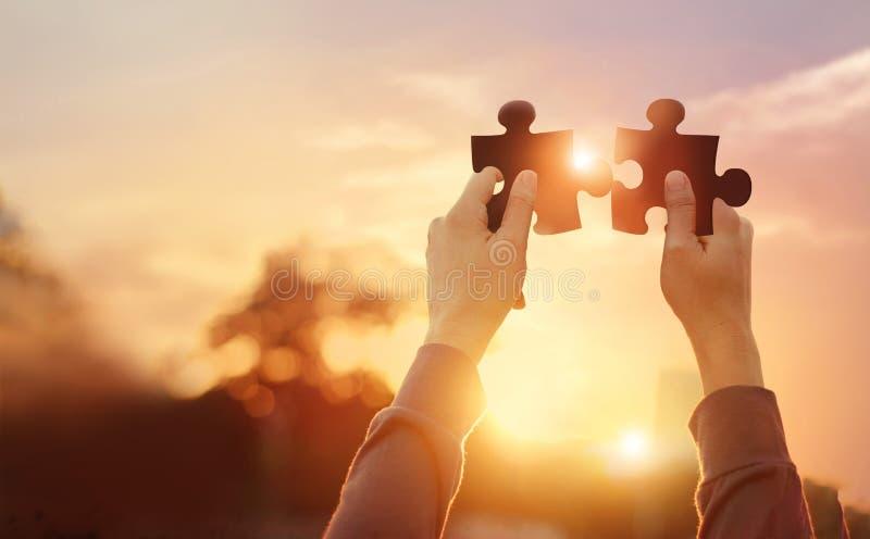 Affär av teamwork, symbol av framgång, pussel, i att förbinda för hand, affärs, planläggning och strategi på solnedgång royaltyfri bild