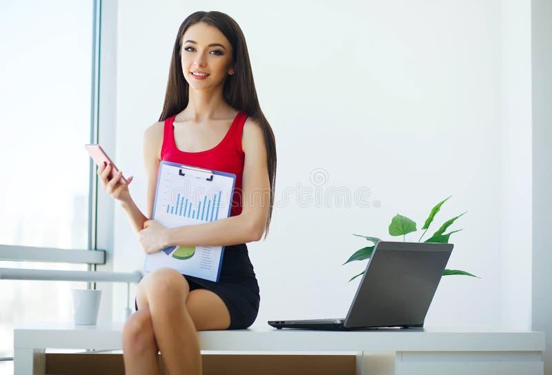 Affär den härliga telefonen talar kvinnan Arbeten, i det ljusa kontoret och att rymma mappen i deras händer lycklig flicka royaltyfri bild