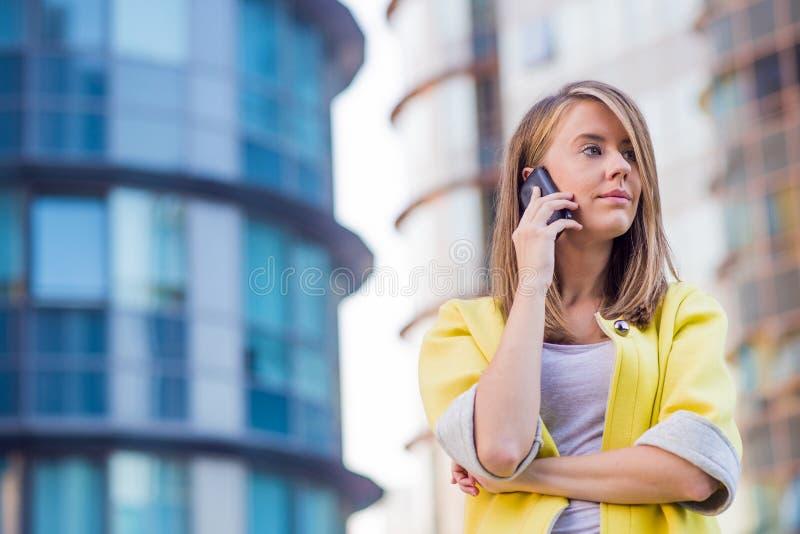 Affär, kommunikation, teknologi och folkbegrepp - ung le affärskvinna som kallar på smartphonen i stad arkivfoto