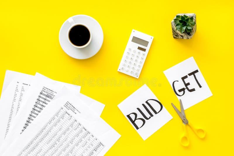 Affär och revisorbegrepp med kaffe, sciccors, den klippta budgetkopian och för gul bästa sikt kontorsbakgrund för räknemaskin arkivfoton