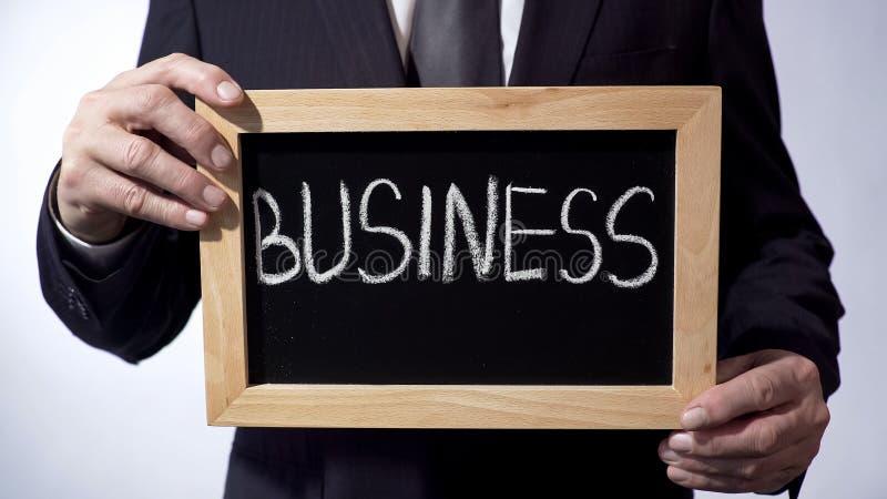 Affär som är skriftlig på svart tavla, man i det hållande tecknet för dräkt, ledarskap, mål arkivfoto