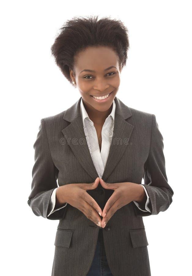 Affär: tillfredsställd svart kvinna som ser kameran som isoleras på wh arkivbilder