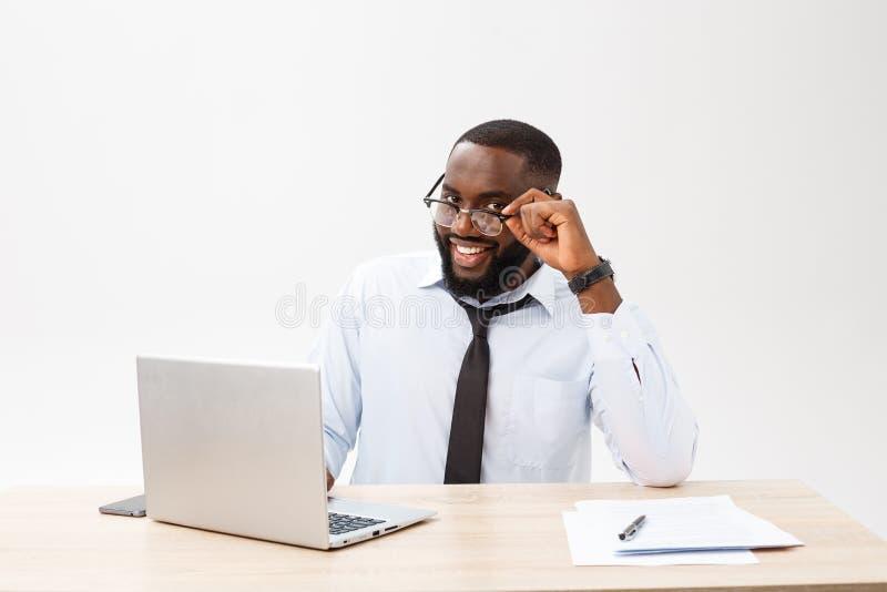 Affären är hans liv Gladlynt ung afrikansk man i formella kläder och arbeta på bärbara datorn arkivfoto