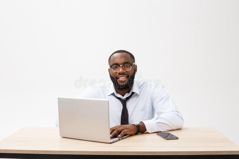 Affären är hans liv Gladlynt ung afrikansk man i formella kläder och arbeta på bärbara datorn royaltyfria bilder