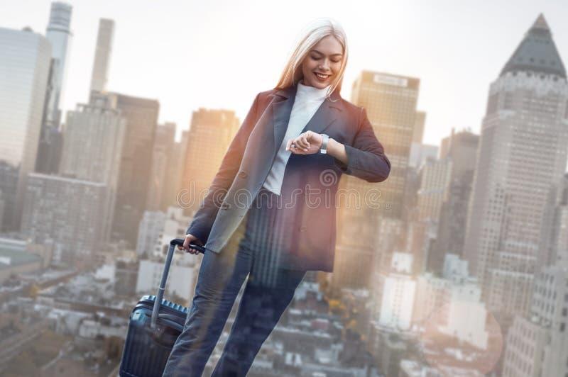 affären time till Gladlynt affärskvinna i klassiska kläder som kontrollerar tiden och ler stundanseende mot av arkivfoton