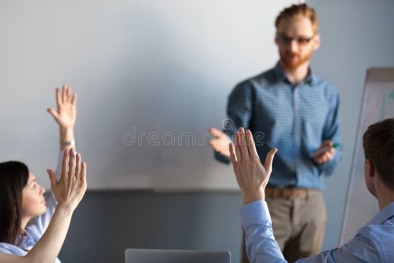 Affärsåhörare som lyfter händer upp röstning som, ställa upp som frivillig på meetien fotografering för bildbyråer