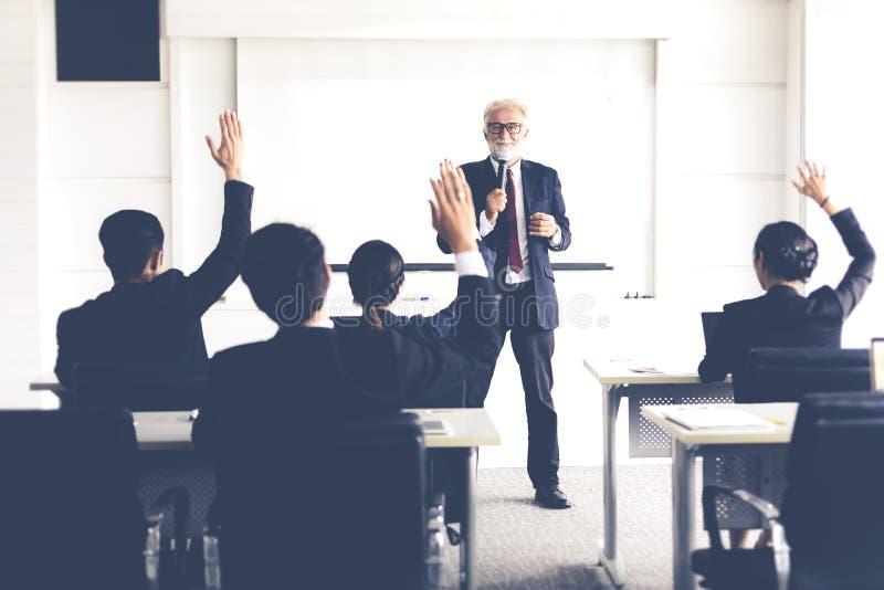 Affärsåhörare som lyfter upp handen, medan affärsmannen talar i utbildning för åsikt med möteledaren i konferensrum royaltyfri bild