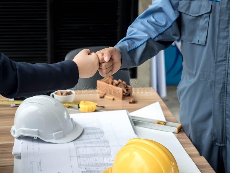 Affärs-, byggnads-, teamwork-, gest- och folkbegrepp - grupp av att le byggmästare i hardhats som hälsar sig med handen royaltyfria foton