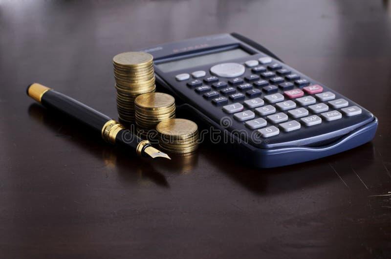 Affärs- och finansbegrepp med reservoarpennan och räknemaskinen mo royaltyfri bild