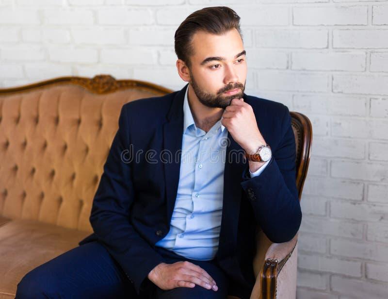 Affärs-, rikedom- och framgångbegrepp - stiligt mansammanträde på royaltyfria bilder