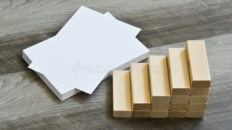 Affärs-/utbildningsutmaningbegrepp - tomma indexkort med trappan uppåt av byggnadskvarter över mörk träbakgrund arkivbild